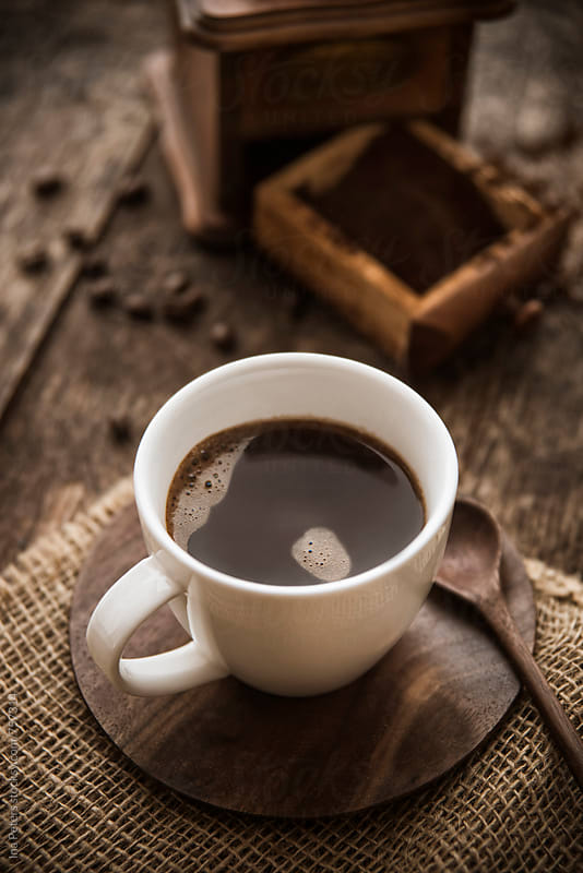 Coffee in a cup with ground coffee and beans by Ina Peters for Stocksy United