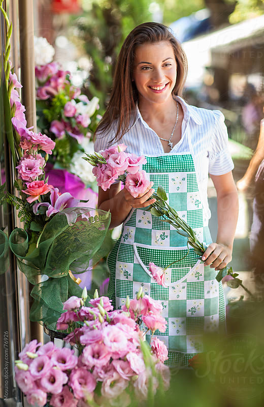 Florist standing in front of the flower shop. by Mosuno for Stocksy United
