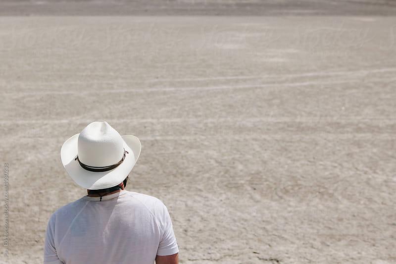 Backside view of man wearing white cowboy hat in desert by Paul Edmondson for Stocksy United