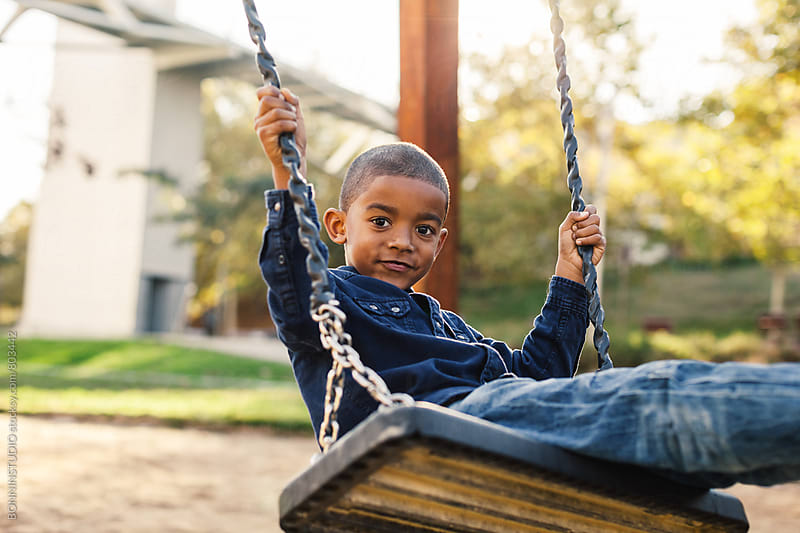 Black boy playing on a playground swing.  by BONNINSTUDIO for Stocksy United