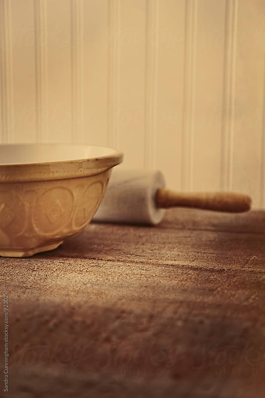 Vintage mixing bowl with rolling pin on wooden table by Sandra Cunningham for Stocksy United