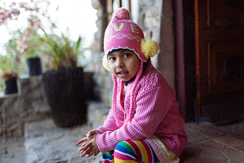 Child in wool knit hat sitting by the door and looking at camera by Saptak Ganguly for Stocksy United