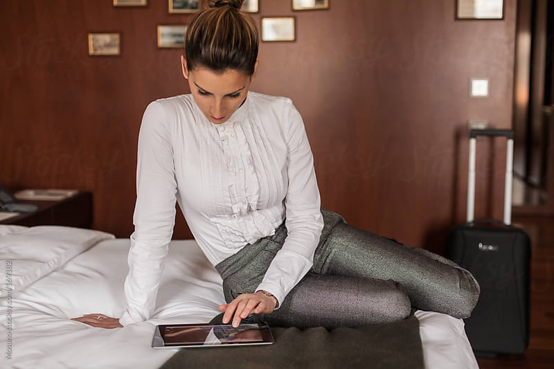 Businesswoman in a Hotel Room Looking at Tablet Computer by Mosuno for Stocksy United