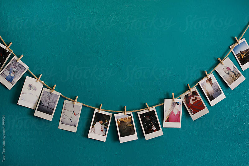A string of mini polaroid pictures on a wall by Tana Teel for Stocksy United
