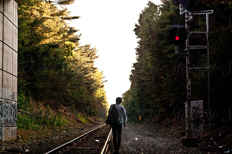 Young man on train tracks by Joe St.Pierre Photography for Stocksy United