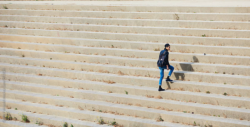 Man with backpack climbing the stairs by Guille Faingold for Stocksy United