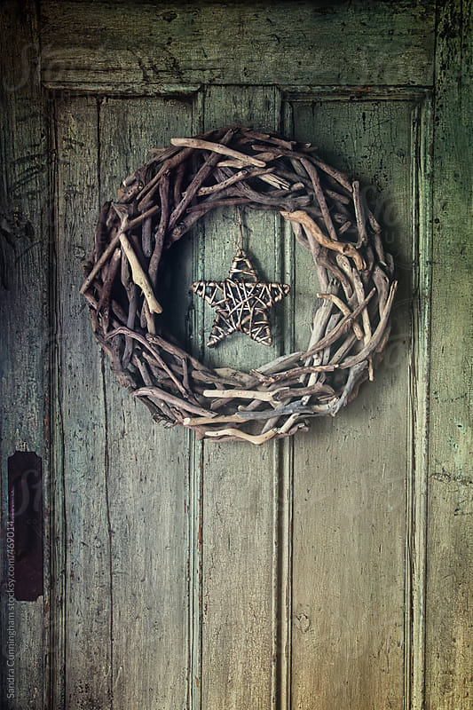 Holiday wreath made of pieces of driftwood on old door by Sandra Cunningham for Stocksy United