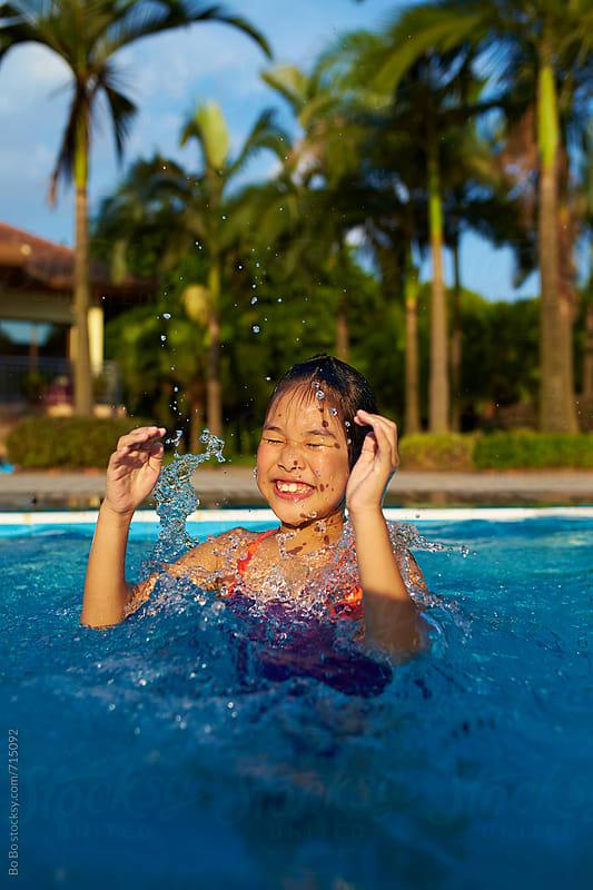 little asian girl having fun in swimming pool by cuiyan Liu for Stocksy United