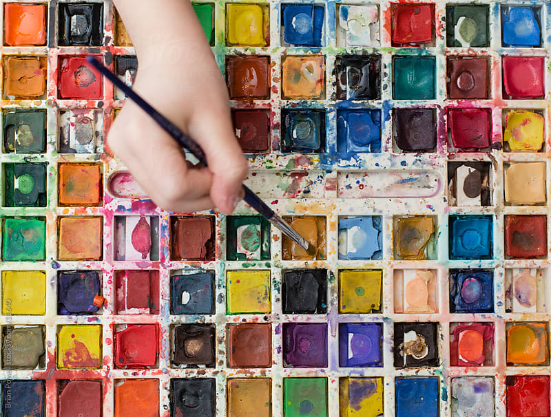 closeup of watercolor paints with hands by Brian Powell for Stocksy United