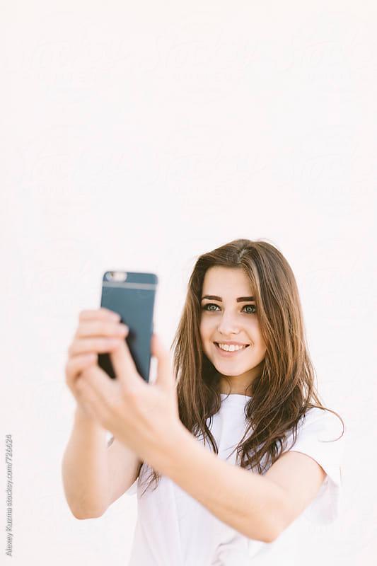 happy woman taking a selfie by Alexey Kuzma for Stocksy United