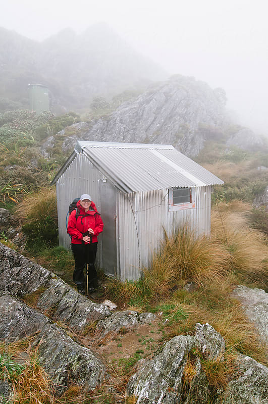 Woman trekker outside Adelaide Tarn Hut, Kahurangi National Park, New Zealand. by Thomas Pickard for Stocksy United