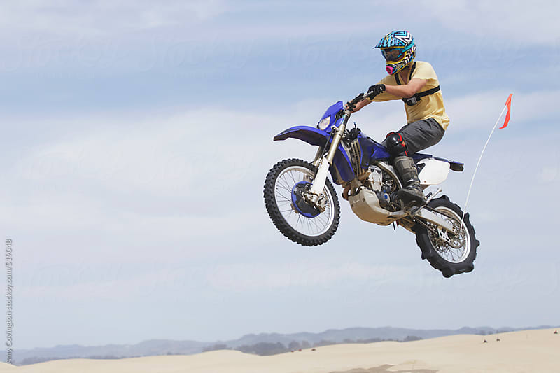 Young man jumping a dirt bike on the sand dunes by Amy Covington for Stocksy United