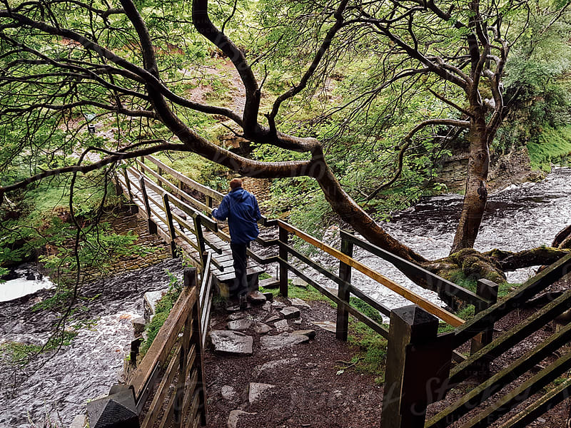 Young male walking his dog over a wooden footbridge above a swollen river. Derbyshire, UK. by Liam Grant for Stocksy United