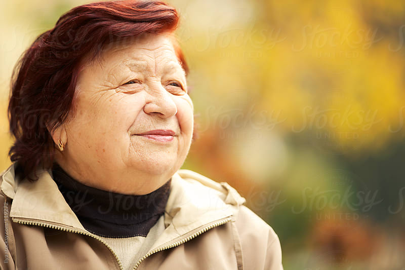 Close-up of a senior woman outdoors by Ilya for Stocksy United
