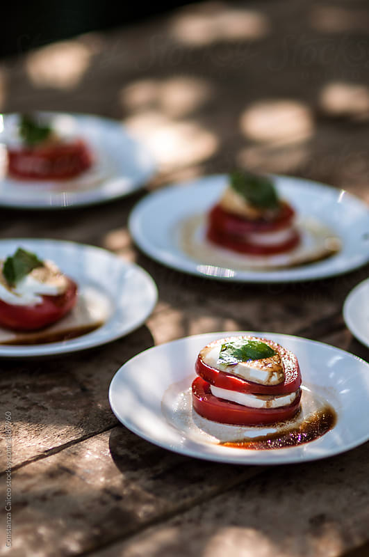 Tomato goat cheese and basil appetizer dishes set on top of a rustic table  by Constanza Caiceo for Stocksy United