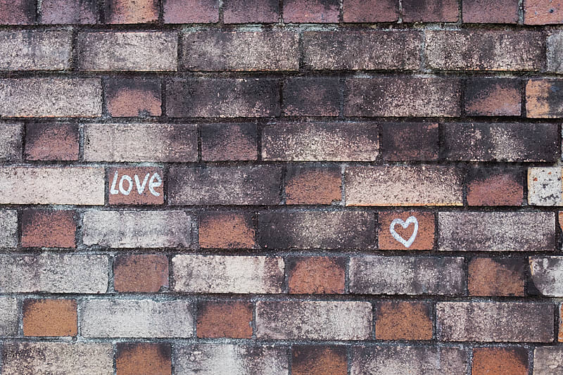 The word LOVE and a LOVEHEART  written on the wall by Rowena Naylor for Stocksy United