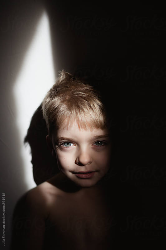 Portrait of blonde boy child in strong light with shadow all around him. by Julia Forsman for Stocksy United