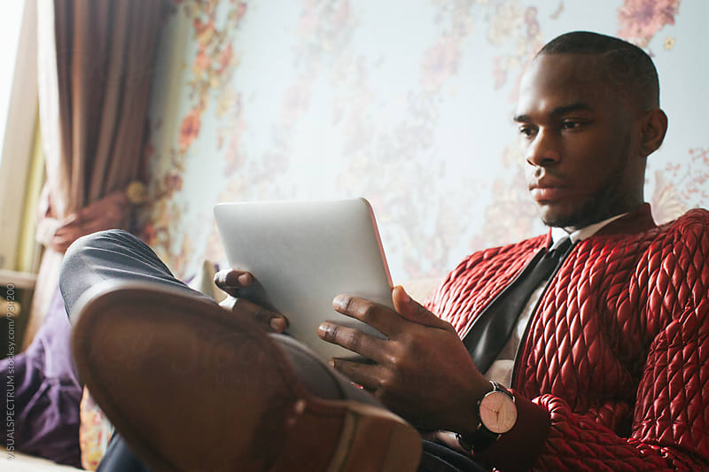 Stylish Young Black Man Sitting on Sofa and Reading on Tablet by Julien L. Balmer for Stocksy United