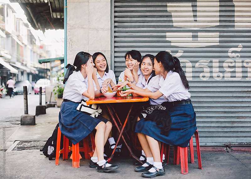 Thai high school student sitting at street restaurant in Bangkok by Nabi Tang for Stocksy United