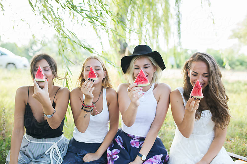 Female friends eating watermelon outside in nature by Jovana Rikalo for Stocksy United