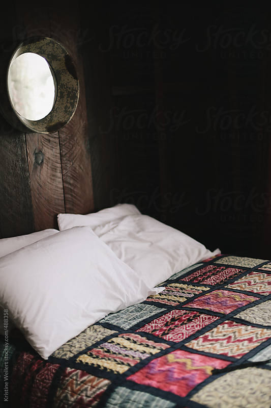 A made bed with a colorful quilt by Kristine Weilert for Stocksy United