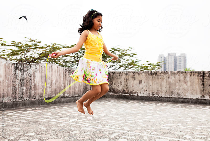 A girl is exercising with jumping rope in a rooftop of urban area by PARTHA PAL for Stocksy United