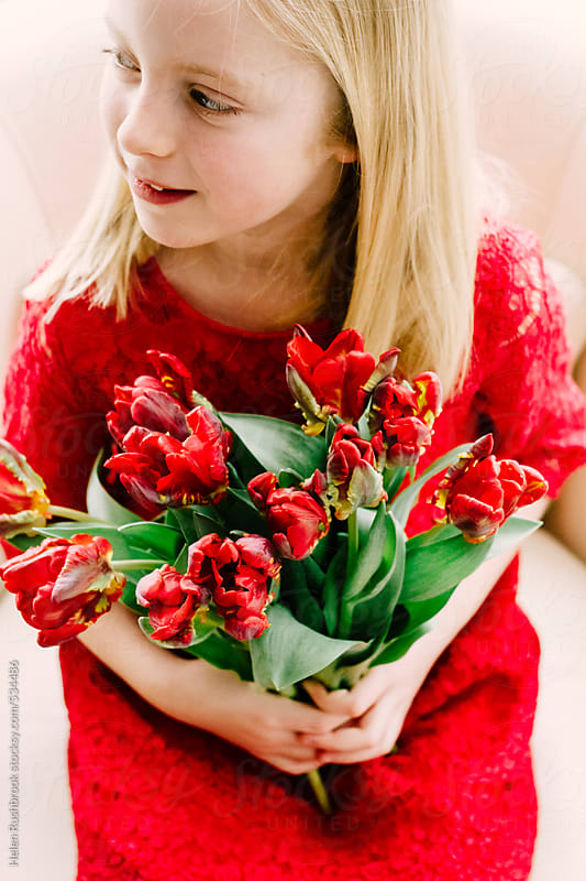 A little girl in a red dress holding a bunch of red tulips. by Helen Rushbrook for Stocksy United