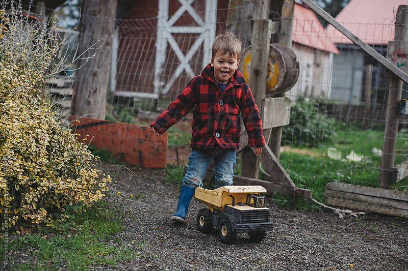 Cute little boy in plaid jacket pushing dumptruck at farm by Rob and Julia Campbell for Stocksy United