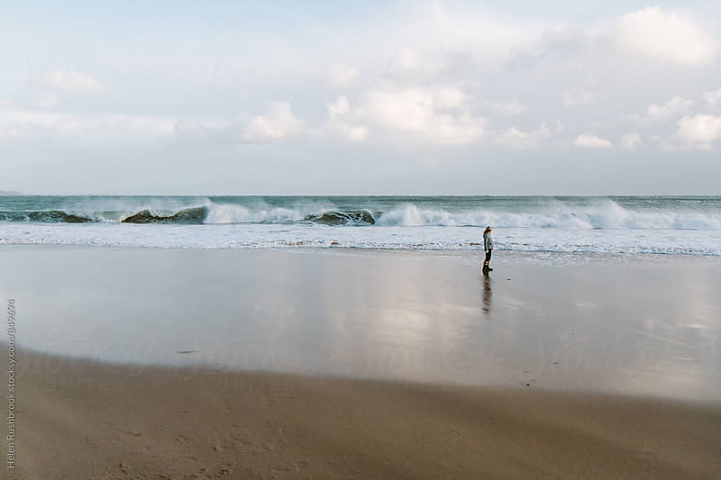 Distant figure of a little girl on a beach in winter. by Helen Rushbrook for Stocksy United