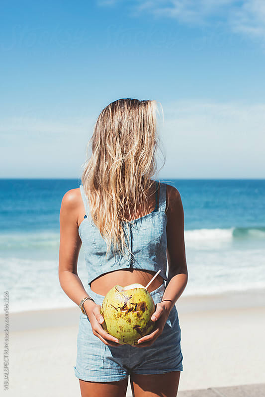 Slim Young Blonde Holding Fresh Coconut and Looking Away by VISUALSPECTRUM for Stocksy United