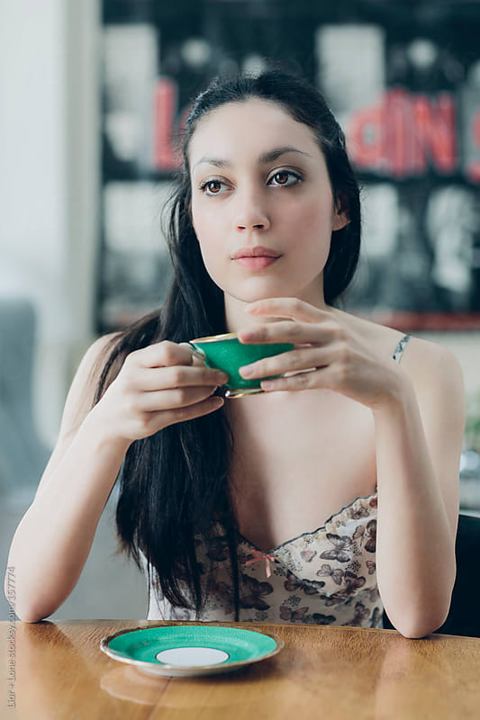 Young attractive woman having tea by Lior + Lone for Stocksy United
