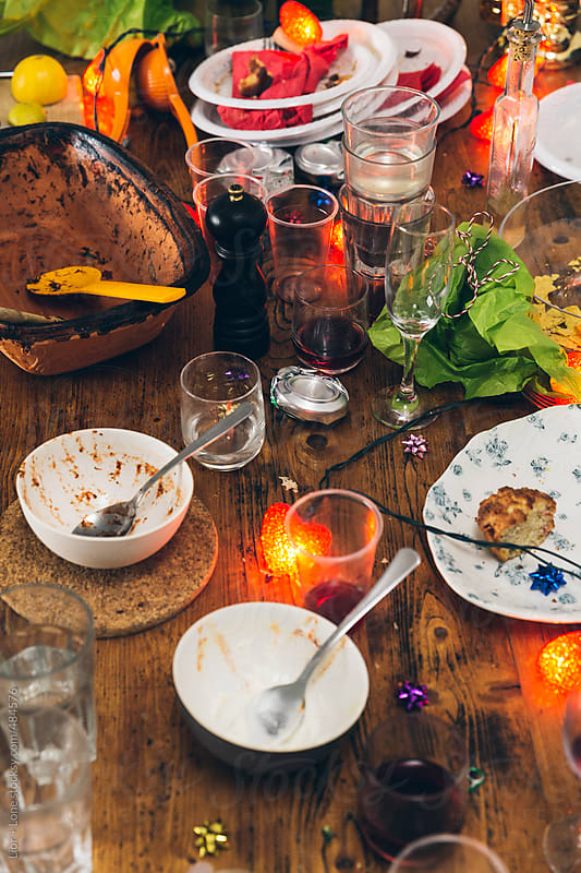 Closeup of table with dirty dishes the day after a party by Lior + Lone for Stocksy United