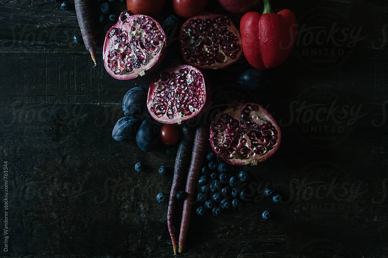 Dark purple and red fruits and vegetables styled on dark wood table by Daring Wanderer for Stocksy United