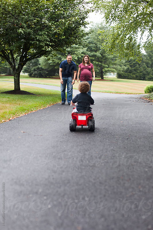 A child rides his motorized toy bike towards his waiting parents. by Holly Clark for Stocksy United
