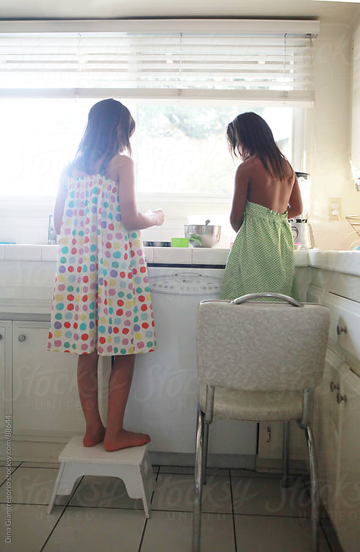 Two girls helping each other standing on chairs in kitchen by Dina Giangregorio for Stocksy United