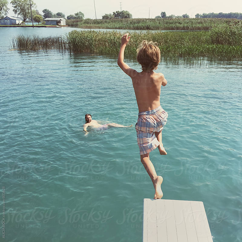 A Boy Jumping Off A Diving Board Into A Summer Lake While His Dad Watches From The Water by ALICIA BOCK for Stocksy United