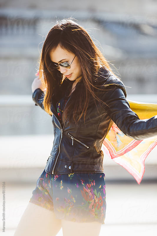 An asian lady wearing sunglasses plays with her yellow scarf on a city balcony by Maresa Smith for Stocksy United