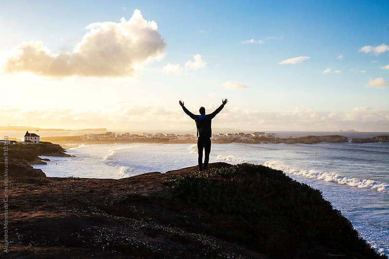 Man standing on the edge of a hill with his arms open in the air in front of the sea and houses during sunset by Alejandro Moreno de Carlos for Stocksy United