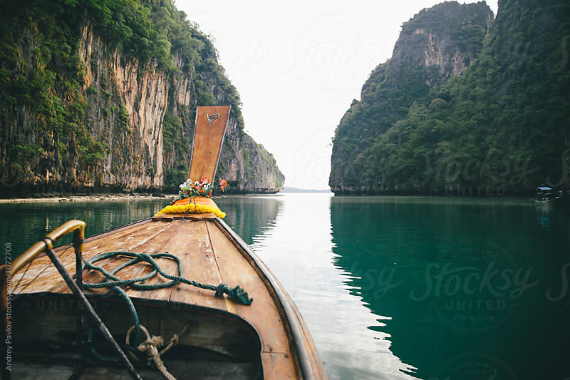 Boat floating on tranquil water surface by Andrey Pavlov for Stocksy United
