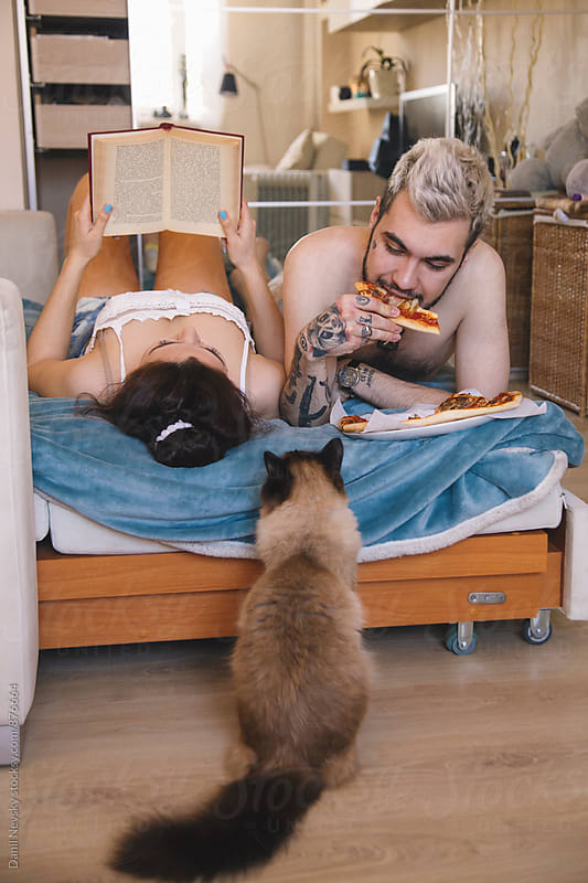 Couple lying on bed. Man eating pizza, woman reading book by Danil Nevsky for Stocksy United
