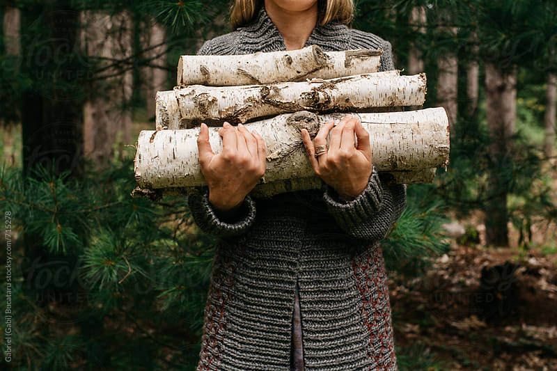 Woman in front of forest with firewood by Gabriel (Gabi) Bucataru for Stocksy United