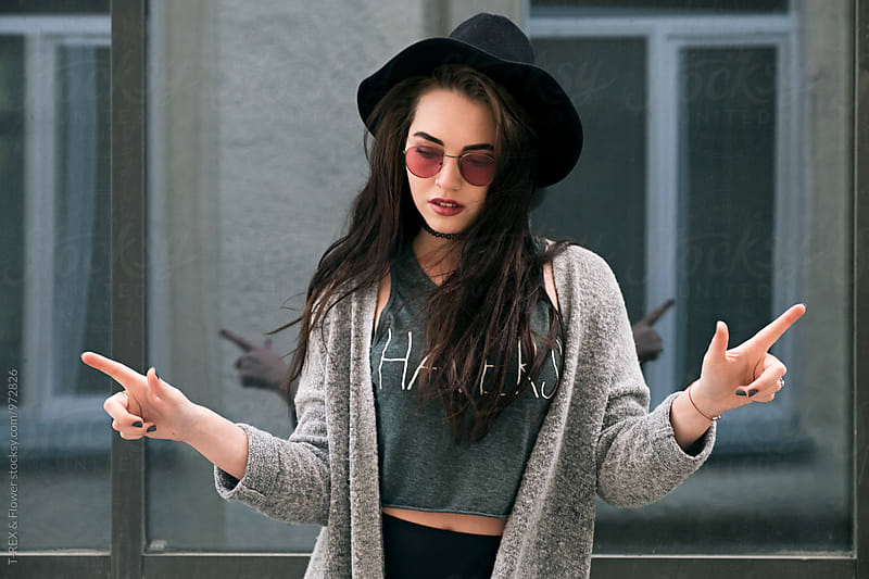 Calm woman in hat and sunglasses with fingers up by Danil Nevsky for Stocksy United