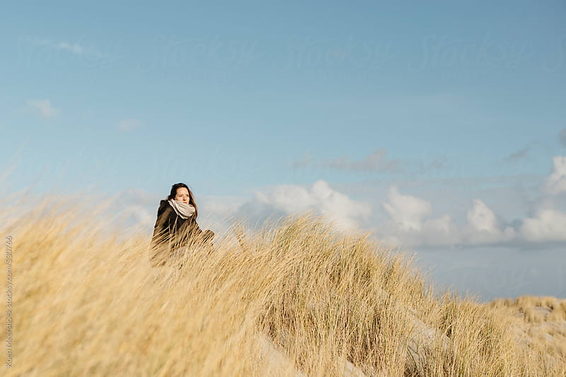 Young woman sits in between dune grass in the dunes. by Koen Meershoek for Stocksy United