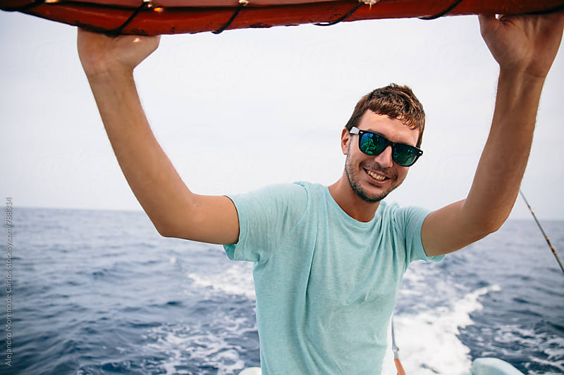 Young smiley man with sunglasses portrait looking at camera during a boat trip with the ocean water behind by Alejandro Moreno de Carlos for Stocksy United