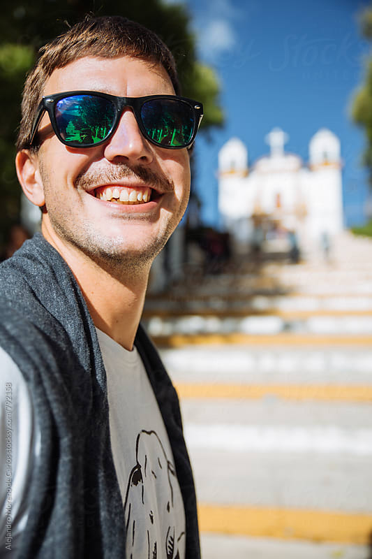 Young smiley man with sunglasses portrait at the steps of a colonial church by Alejandro Moreno de Carlos for Stocksy United