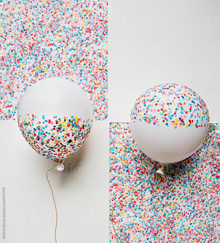 2 balloons arranged playfully with their confetti covered part and empty part by Beatrix Boros for Stocksy United
