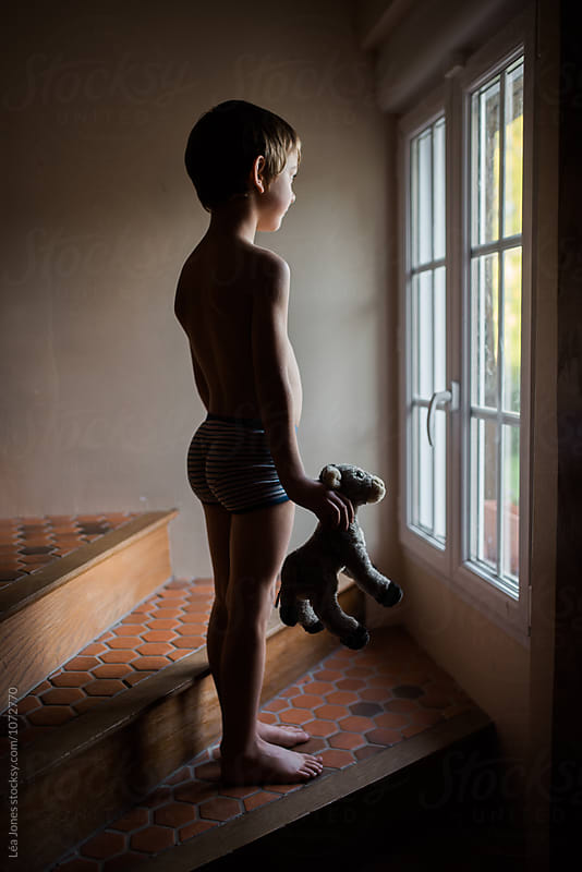 boy standing by window with stuffed donkey in hands by Léa Jones for Stocksy United