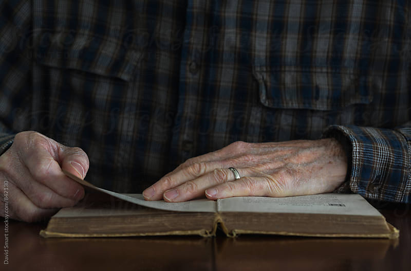 Close-up of a senior man's hands on the pages of an old book. by David Smart for Stocksy United