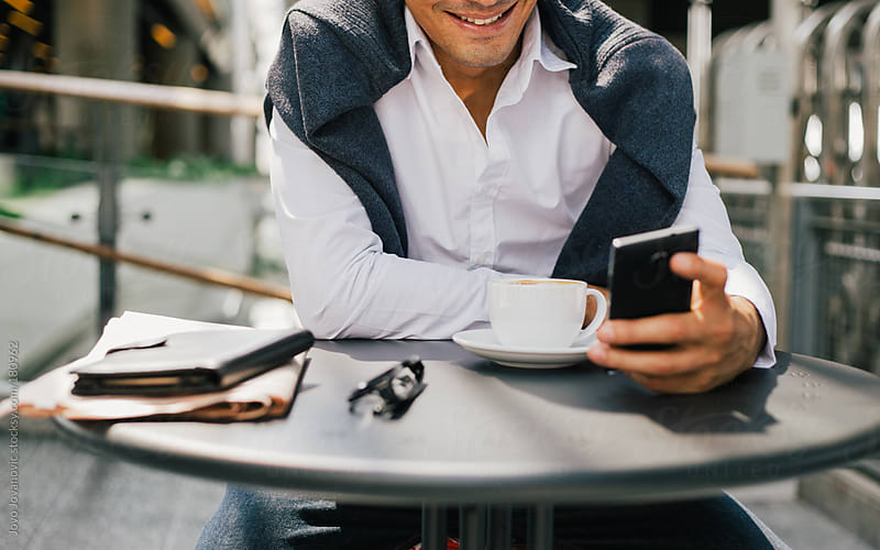 Businessman smiling and checking his smartphone by Jovo Jovanovic for Stocksy United