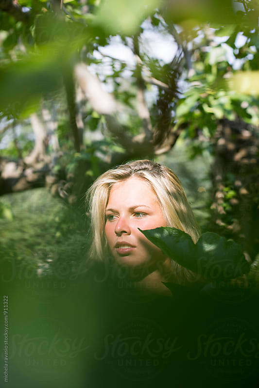 Blonde girl standing in the leaves of a plant in the nature by michela ravasio for Stocksy United